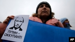 "A woman holds a banner that reads: ""Putin is Occupier"" during a rally against the breakup of the country in Simferopol, Crimea, Ukraine, March 11, 2014."