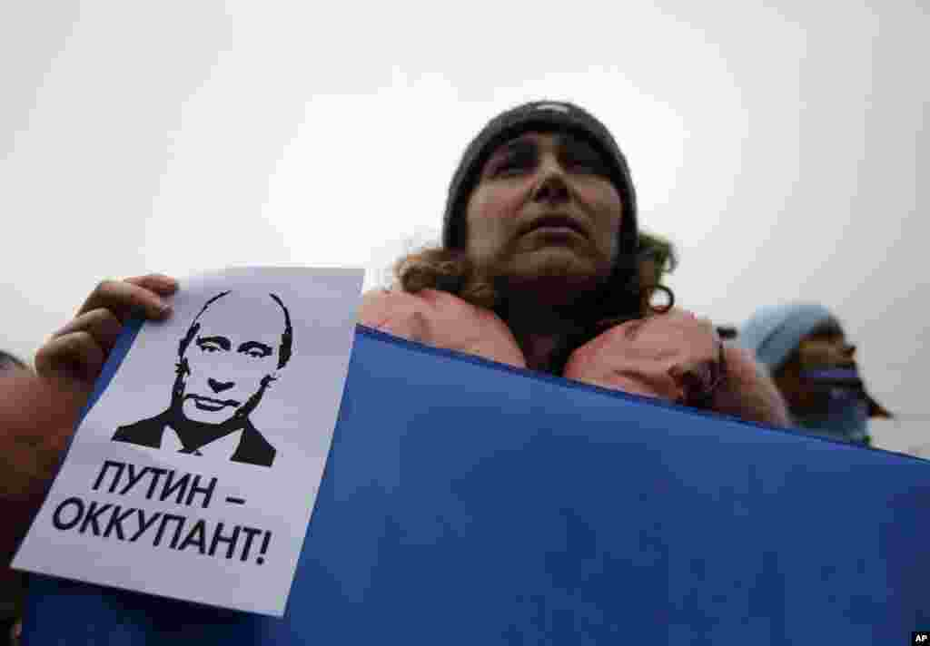"A woman holds a banner that reads: ""Putin is Occupier"" during a rally against the breakup of Ukraine in Simferopol, Crimea, Ukraine, March 11, 2014."