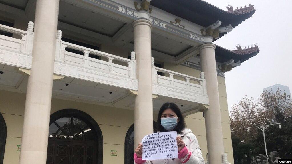 2020年12月10日(世界人权日),武汉市民姚青在地方政府办公地点举牌维权(资料照片)(photo:VOA)