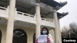 2020年12月10日(世界人权日),武汉市民姚青在地方政府办公地点举牌维权(资料照片)