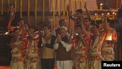 Japan's Prime Minister Shinzo Abe (front, 3rd L) and his Indian counterpart Narendra Modi perform a religious ritual during evening prayers on the banks of the river Ganges in Varanasi, India, December 12, 2015.