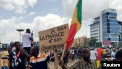 Opposition supporters react to the news of a possible mutiny of soldiers in the military base in Kati, outside the capital Bamako, at Independence Square in Bamako, Mali, Aug. 18, 2020.