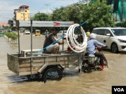 Drivers travel through a flooded street following recent rains in Phnom Penh, Cambodia, October 12, 2020. (Hul Reaksmey/VOA Khmer)