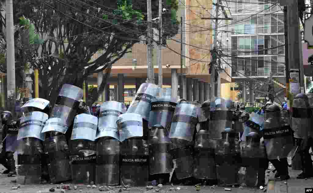 Honduran riot police take cover during clashes with students of the National Autonomous University of Honduras (UNAH) and elementary school teachers protesting against the approval of education and healthcare bills in the Honduran Congress in Tegucigalpa, April 29, 2019.