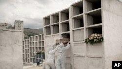 Pekerja pemakaman menempatkan peti mati berisi jenazah Jose de Arimateia, 65, yang meninggal karena komplikasi terkait Covid-19, ke dalam ceruk di pemakaman kota di Nova Iguacu, Brazil, 24 September 2020. (Foto: AP/Silvia Izquierdo )