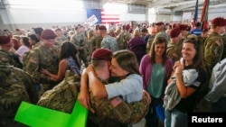 FILE - John Jacoby, a paratrooper with the 1st Brigade Combat Team, 82nd Airborne Division, hugs his girlfriend Emiliee Chance after returning home from Afghanistan at Pope Army Airfield in Fort Bragg.