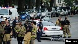 Nhân viên khẩn cấp đứng gần một chiếc xe cảnh sát sau vụ nổ súng bên ngoài tòa nhà Quốc hội ở Washington, ngày 3/10/2013.