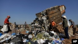 FILE - In this Aug. 27, 2014 photo, workers gather around a truck dumping trash at the Estrutual landfill in Brasilia, Brazil. The city government announced it would shut down the landfill and replace it with a new one in the district of Samambaia, located farther away from the presidential palace. (AP Photo/Eraldo Peres)