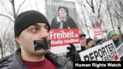 Members of Journalists Without Borders protest against Azerbaijan's President Ilham Aliyev during his visit to meet German Chancellor Angela Merkel, in front of the Chancellery in Berlin, January 21, 2015. REUTERS/Fabrizio Bensch (GERMANY - Tags: POLI