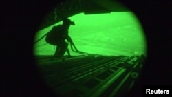 A still image captured from the U.S. Central Command night vision video footage shows an Air Force personnel retrieving straps after the U.S. military airdrop of food and water for thousands of Iraqi citizens threatened by the Islamic State of Iraq and th