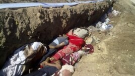 This citizen journalism image provided by Shaam News Network SNN, taken on Sunday, Aug. 26, 2012, purports to show people killed by shabiha, pro-government militiamen, being buried in a mass grave in Daraya, Syria. According to activists' accounts, govern