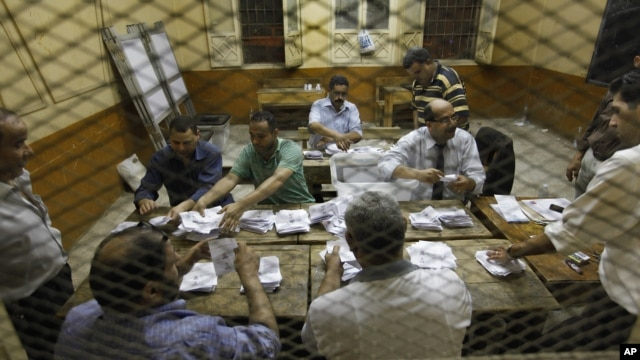 Egyptian elections officials count ballots at a polling center during the second day of the presidential runoff, in Cairo, Egypt, Sunday, June 17, 2012.