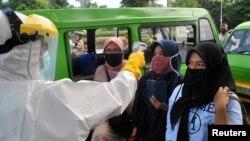 Petugas memeriksa suhu tubuh para penumpang angkot di Bogor, Jawa Barat, 8 April lalu (foto: ilustrasi).