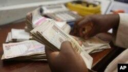 Seorang pegawai pertukaran uang menghitung mata uang naira di Lagos, Nigeria.