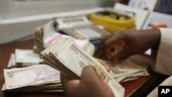 FILE - A money changer counts Nigerian naira currency in Lagos, Nigeria, Oct. 20, 2015.