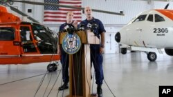Capt. Mark Fedor (r) chief of response for the Coast Guard 7th District, talks to during a news conference as Lt. Commander Gabe Somma (l) listens, Oct. 5, 2015, at the Opa-locka Airport in Opa-locka, Fla.