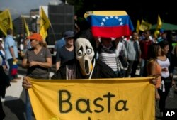"FILE - A protester, wearing a Ghostface mask and holding a banner that reads in Spanish, ""Stop,"" takes part in a protest against President Nicolas Maduro, in Caracas, Venezuela, Oct. 26, 2016."
