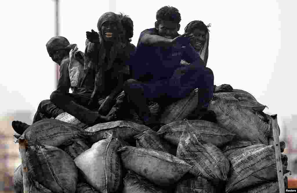 Coal workers travel on the back of a truck in Barsana, India.