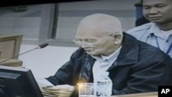 Nuon Chea, former deputy secretary in the Communist Party of Kampuchea, reading his documents is seen on a local TV at a restaurant in Phnom Penh, file photo.