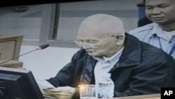 Nuon Chea, former deputy secretary in the Communist Party of Kampuchea, reading his documents is seen on a local TV at a restaurant in Phnom Penh, Tuesday, Nov. 22, 2011. The Khmer Rouge carried out its policies for the sake of the Cambodian people and to