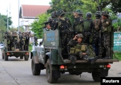 FILE - Government soldiers are seen atop military vehicles during their assault against rebels from the Maute group, who last year took over large parts of Marawi City, southern Philippines, June 13, 2017.