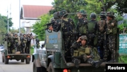 FILE - Government soldiers are seen onboard military vehicles driving along the main road of Amai Pakpak as the assault continues against insurgents from the Maute group, who have taken over large parts of Marawi City, Philippines, June 13, 2017.