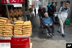 In this April 13, 2016 photo, shoppers past by traditional food on sale in Beijing. China's economic growth slowed in the first quarter to 6.7 percent compared with the previous year, according to official data released on April 15, 2016.