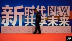 一名警卫在上海中国国际进口博览会的口号前走过。(2018年11月5日)