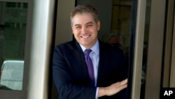 CNN's Jim Acosta walks out of the U.S. District Courthouse with a smile, Nov. 16, 2018, in Washington.
