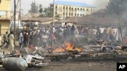 Warga Nigeria berkerumun di dekat lokasi ledakan bom di Kaduna, Nigeria utara (8/4).