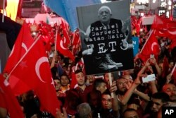 "FILE - Supporters of Turkish President Recep Tayyip Erdogan wave their national flags and hold a portrait of Fethullah Gulen, a U.S.-based Muslim cleric, with Turkish words that read: ""the Coup nation traitor, FETO"" (Feto is the nickname of Fethullah Gulen), during a pro-government rally at Kizilay main square, in Ankara, Turkey, July 20, 2016."