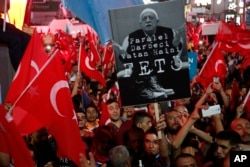 "Supporters of Turkish President Recep Tayyip Erdogan wave their national flags and hold a portrait of Fethullah Gulen, a U.S.-based Muslim cleric, with Turkish words that read: ""the Coup nation traitor, FETO"" (Feto is the nickname of Fethullah Gulen)."