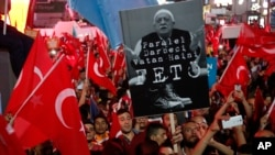 "Supporters of Turkish President Recep Tayyip Erdogan wave their national flags and hold a portrait of Fethullah Gulen, a U.S.-based Muslim cleric, with Turkish words that read: ""the Coup nation traitor, FETO"" (Feto is the nickname of Fethullah Gulen), du"