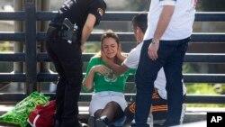 Petugas medis memeriksa seorang perempuan yang terguncang setelah seorang tentara ditikam di Tel Aviv, Israel (10/11).