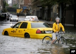 FILE - A bicyclist makes his way past a stranded taxi on a flooded New York City street as Tropical Storm Irene passes through the city, Aug. 28, 2011. A June 2012 study in Nature Climate Change said scientists and computer models were estimating that by the year 2100, sea levels globally could rise as much as 3.3 feet.