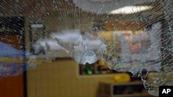 FILE - Glass is shattered at the entrance to Sandy Hook Elementary School in Newtown, Connecticut, after a shooter opened fire inside the school, Dec. 14, 2012.