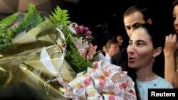 Yoani Sánchez recibe flores en una conferencia en Sao Paulo. En Miami recibirá condecoraciones por su valenteía.