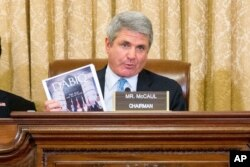 FILE - House Homeland Security Committee Chairman Michael McCaul, R-Texas, center, holds up a copy of Dabiq, the monthly online magazine used by the Islamic State group for propaganda and recruitment, on Capitol Hill in Washington, Oct. 21, 2015.