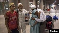 Warga India yang dievakuasi dari Yaman memeluk anaknya saat tiba di bandar udara Mumbai (6/4).