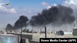 Smoke billows from buildings in the central Syrian town of Talbisseh in Homs province. Russian warplanes carried out airstrikes in three Syrian provinces, including Homs, along with regime aircraft, according to a Syrian security source, Sept. 30, 2015.