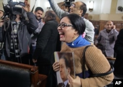 A supporter of ousted President Hisni Mubarak reacts in a courtroom to a verdict ordering a retrial in Cairo, Egypt, Jan. 13, 2015.
