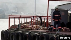 A rescue worker walks past bodies retrieved from the sea after a boat sank in the Bosphorus strait, near Istanbul, November 3, 2014.