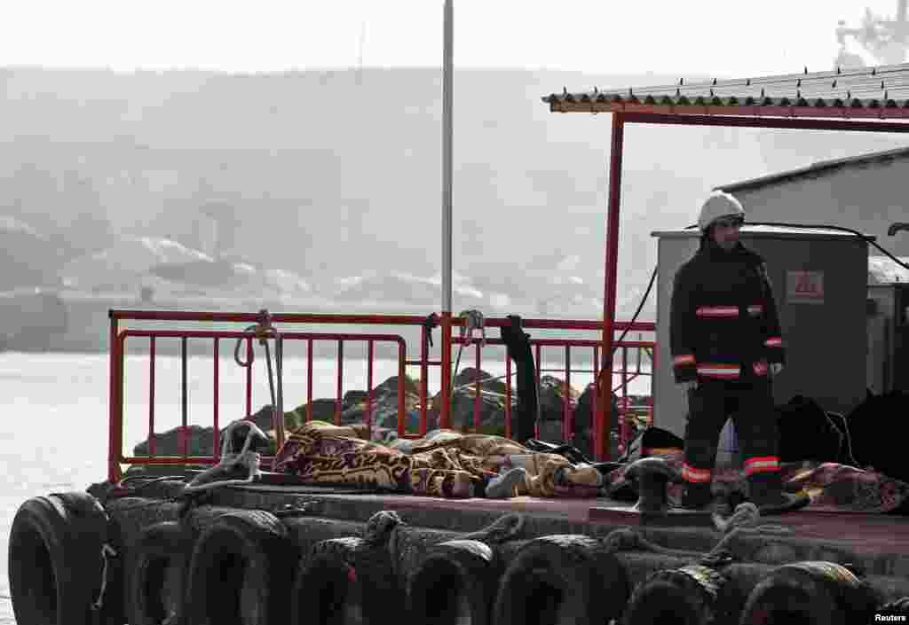 A rescue worker walks past bodies retrieved from the sea after a boat sank in the Bosphorus strait, near Istanbul, Turkey, Nov. 3, 2014.