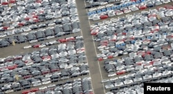 FILE - Cars for export stand in a parking area at a shipping terminal in the harbor of the northern German town of Bremerhaven, Oct. 8, 2012.
