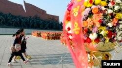 这张共同社拍摄照片显示,在朝鲜劳动党建党69周年之际,朝鲜民众参拜平壤万寿台已故领导人金日成和金正日父子的巨大雕像。(2014年10月10日)