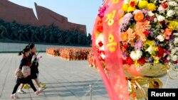 Warga Korea Utara membawa bunga saat mengunjungi patung-patung para mendiang pemimpin negara di Pyongyang.