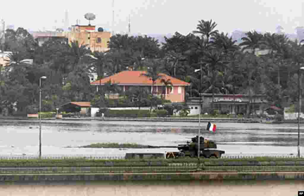 A French tank crosses General de Gaulle bridge in Abidjan, April 5, 2011. (Reuters image)