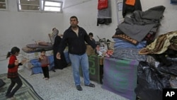 Sufian Wadiya, 36, whose home was destroyed by Israeli strikes during last summer's Israel-Hamas war, stands in front of his 12-member family's belongings at a U.N. school in Gaza City where they now live, Jan. 27, 2015.