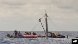 Anggota pasukan penjaga pantai Filipina (kiri) mendekati kapal nelayan yang hampir tenggelam, di perairan dekat kota Zamboanga, selatan Filipina, 10 Januari 2016. (Philippine Coast Guard via AP)