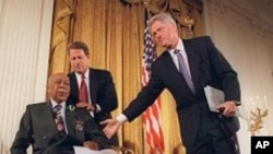 FILE - Then-President Bill Clinton and then-Vice President Al Gore, back, help Herman Shaw, 94, a Tuskegee syphilis study victim, during a news conference on May 16, 1997, when Clinton apologized to blacks whose syphilis went untreated by government doctors.